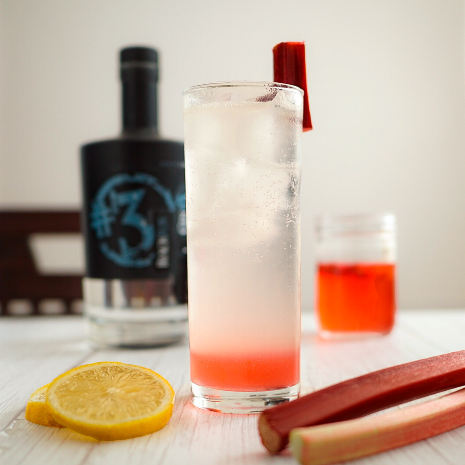 Canadian #3 Gin 750ml bottle and Rhubarb Lemonade cocktail with lemon slices and rhubarb garnish