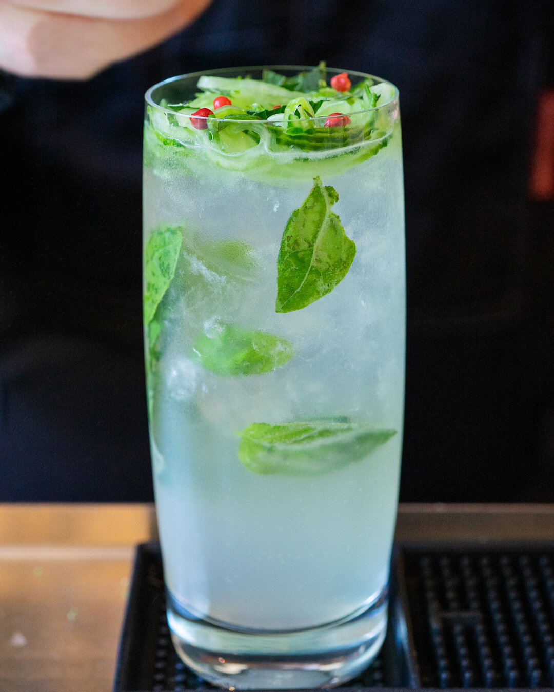 Canadian Gin with Secret Garden cocktail with cucumber slices, lime zest, mint and pink peppercorn garnish