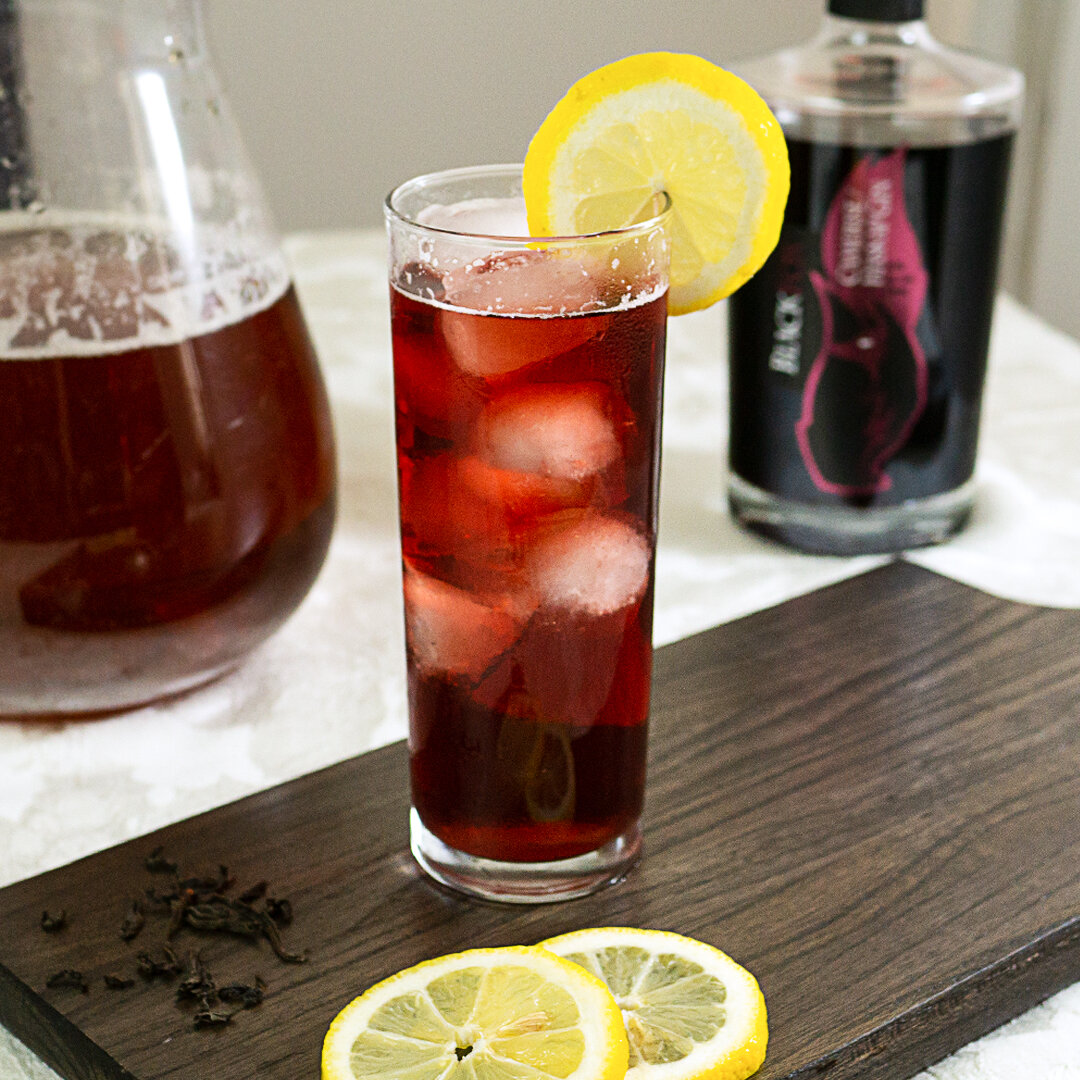 Canadian Gin with 750ml Haskap Gin bottle with Chilled Haskap Sweet Tea cocktail and iced tea pitcher with lemon garnish