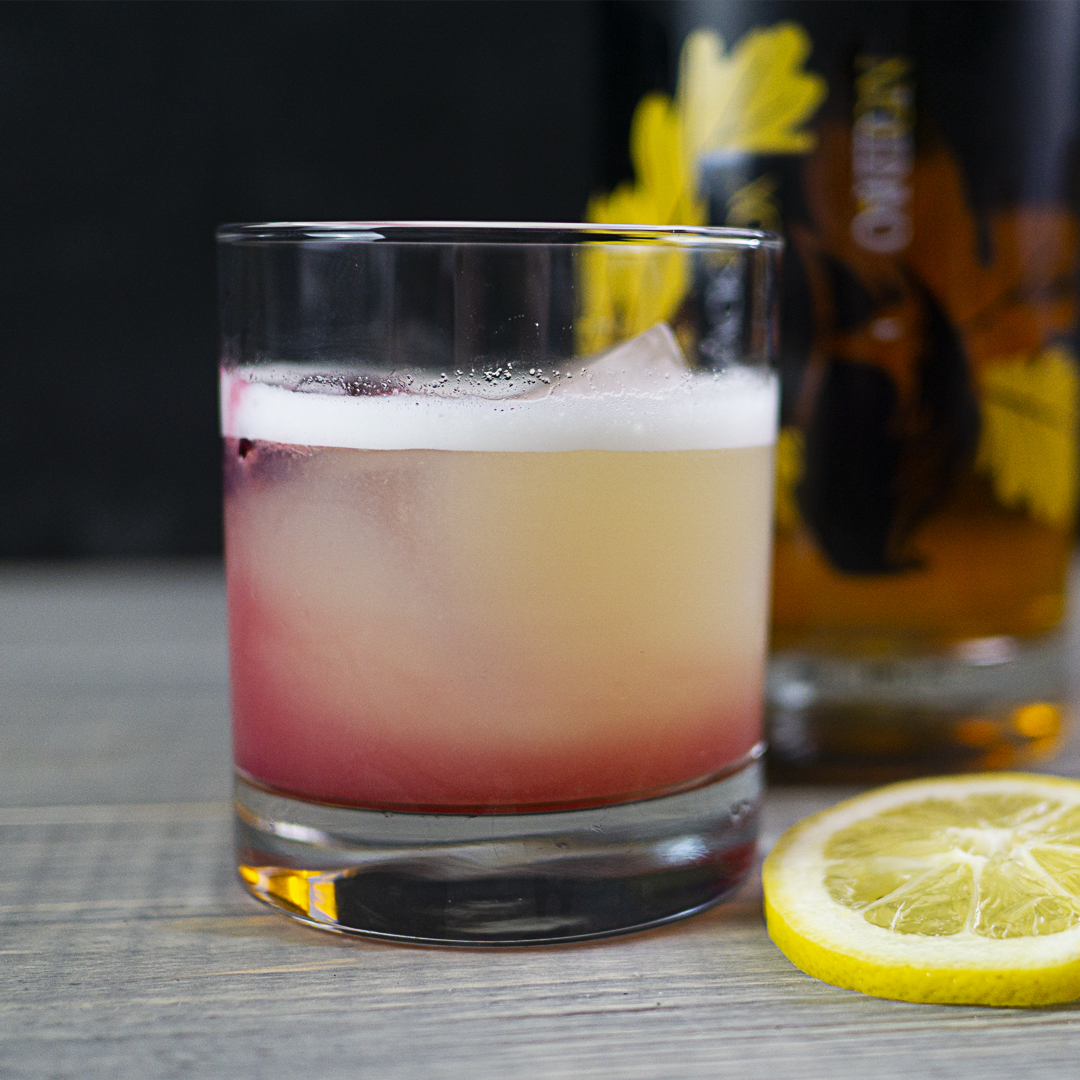 Canadian Oaked Gin with Oaked Gin Sour cocktail and a lemon garnish
